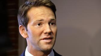 FILE - In this Feb. 6, 2015 file photo, former  U.S. Rep. Aaron Schock speaks to reporters in Peoria, Ill. Another Illinois county has voted to ask former U.S. Rep. Aaron Schock to pay for costs associated with electing his replacement in the 18th District. The McLean County Board has approved sending a letter to the Peoria Republican asking him to pay $200,000 for the July 7 primary and Sept. 10 election. Schock resigned in March after questions arose about his spending. County Board member Mark Johnson says Schock owes the money to taxpayers. (AP Photo/Seth Perlman, File)