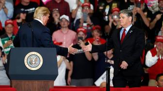 President Donald Trump shakes hands with Fox News Channel's Sean Hannity, right, during a campaign rally Monday, Nov. 5, 2018, in Cape Girardeau, Mo. (AP Photo/Jeff Roberson)