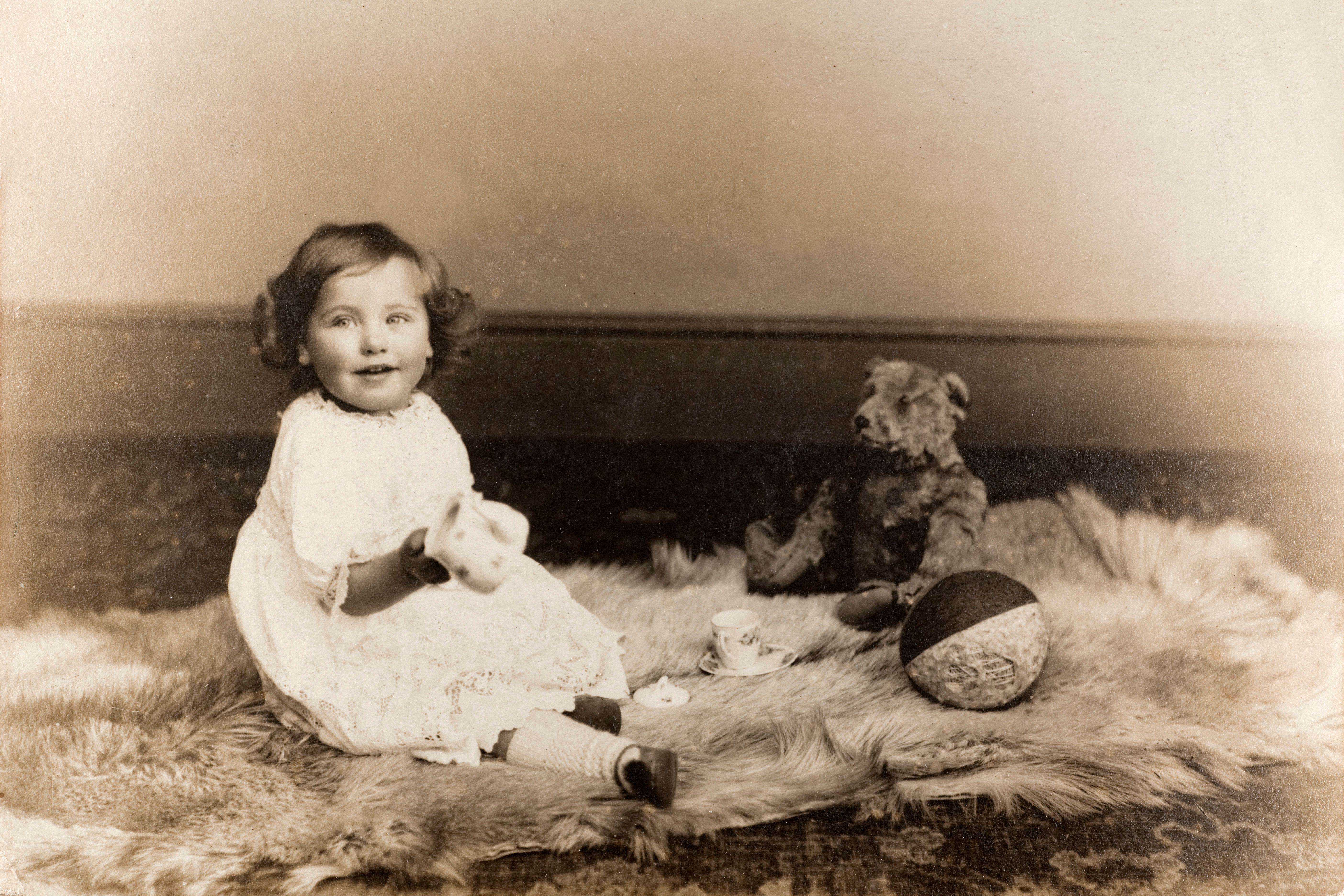 'Vintage black and white photograph of a baby girl sitting on an animal skin rug, with a teddy bear and toys, circa 1910. Some dust and scratches that reflect age of original image. See my vintage images lightbox, including similar baby boy shot...'