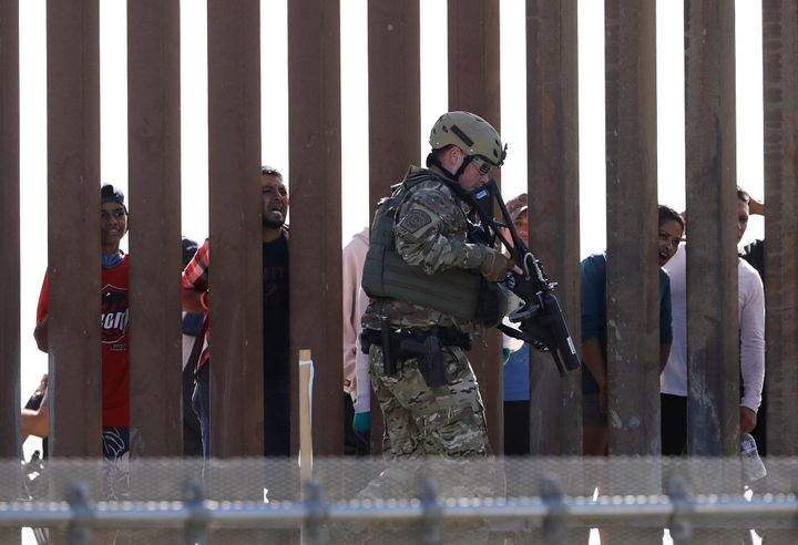 U.S. Customs and Border Protection officers walks along a wall at the border between Mexico and the United States, as seen fr