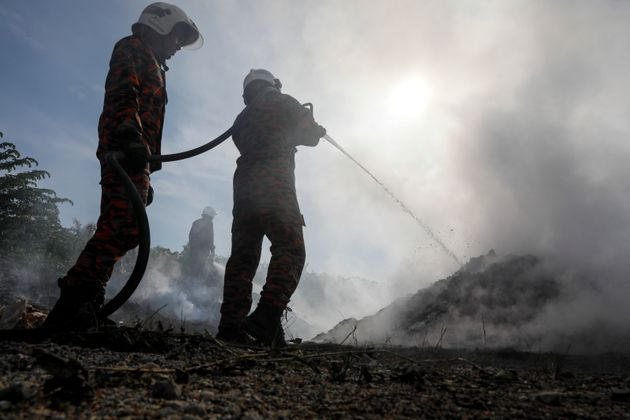 Firefighters put out a blaze at an illegal dumpsite on a palm oil plantation near Jenjarom, Malaysia,...