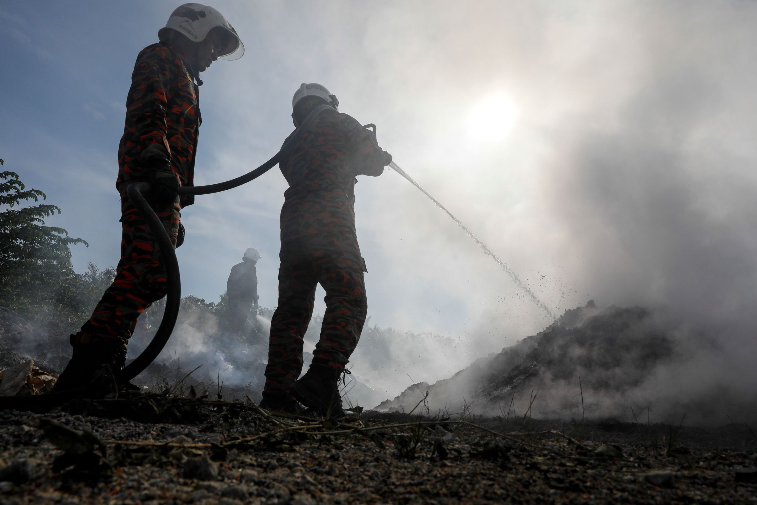 Firemen put out a blaze at a dumpsite on a palm oil plantation near Jenjarom, Feb. 2. Plastic fires are notoriously diff
