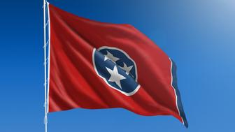 The flag of the state of Tennessee blowing in the wind in front of a clear blue sky