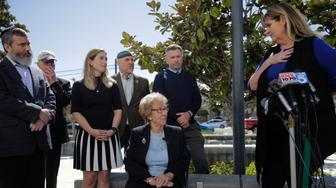 Eva Schloss, center, the stepsister of Anne Frank and a Holocaust survivor, listens to Charlene Metoyer, a board member of the Newport-Mesa Unified School District during a news conference Thursday, March 7, 2019, in Newport Beach, Calif. Schloss has met with Southern California high school students who were photographed giving Nazi salutes around a swastika formed by drinking cups at a party. Schloss says the students apologized for their behavior and indicated they didn't realize what it really meant. (AP Photo/Jae C. Hong)