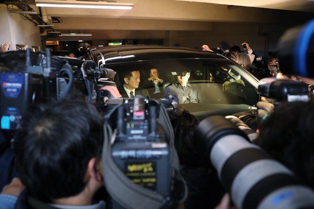 弁護士事務所の前でゴーンの乗った車を取り囲む報道陣