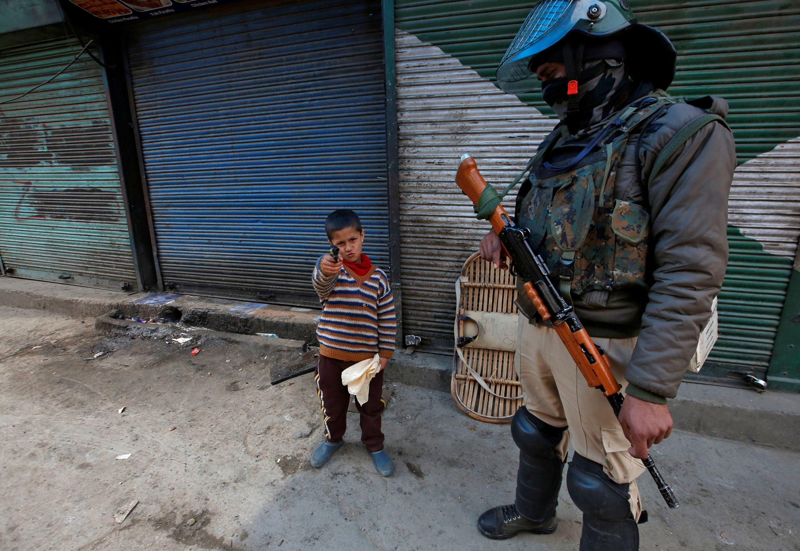 A boy plays with his toy pistol next to an Indian policeman standing guard in front of closed shops during a strike called by