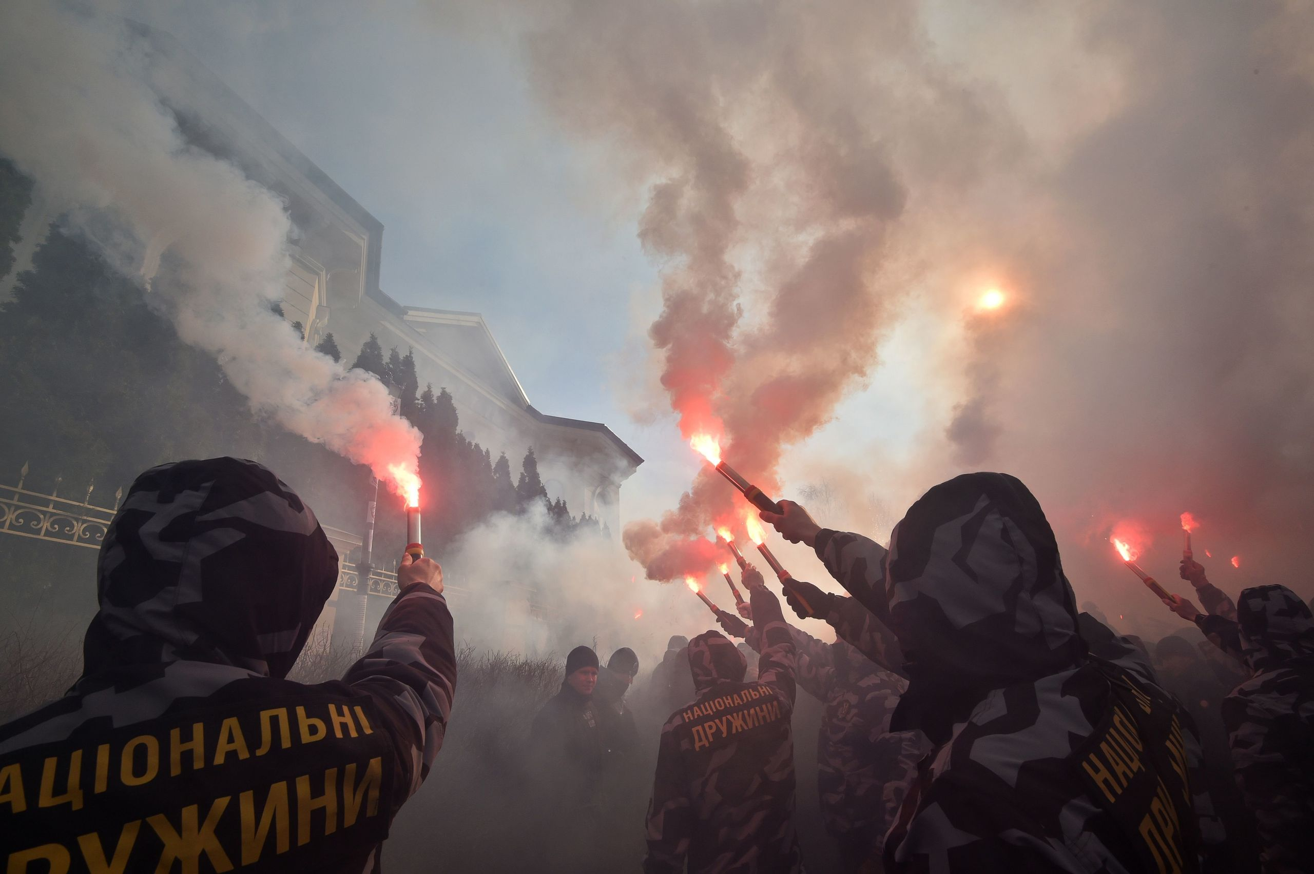 Activists and supporters of the Ukrainian far-right party National Corps burn flares in front of the private house which supp