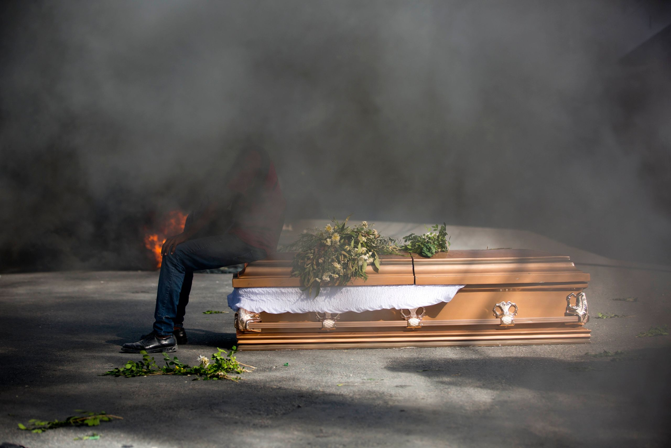 A demonstrator sits on the coffin containing the body of a protester who was killed during previous protests in Port-au-Princ