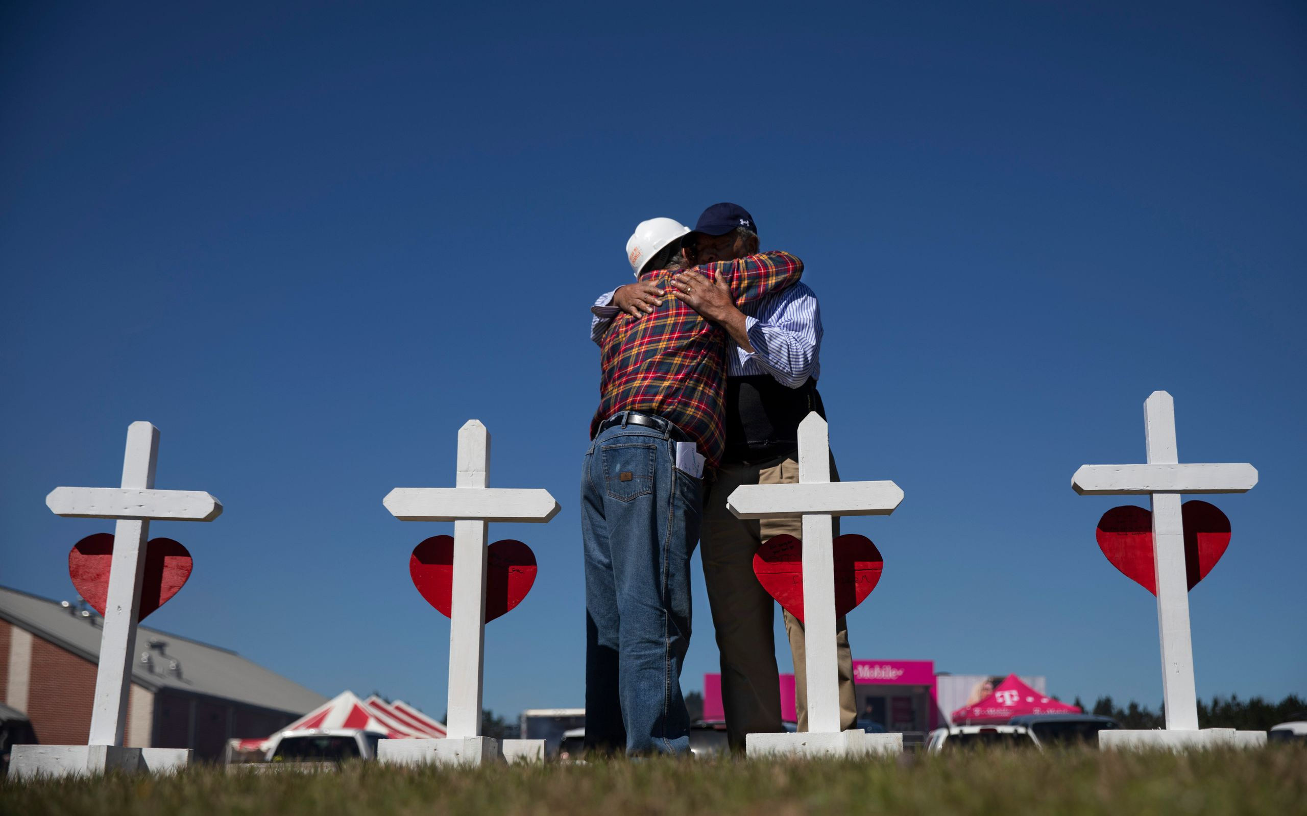 Rev. Arthur Thomas, right, of Mt. Nebo Baptist Church, is embraced by Greg Zanis, who built a cross for each victim of the to