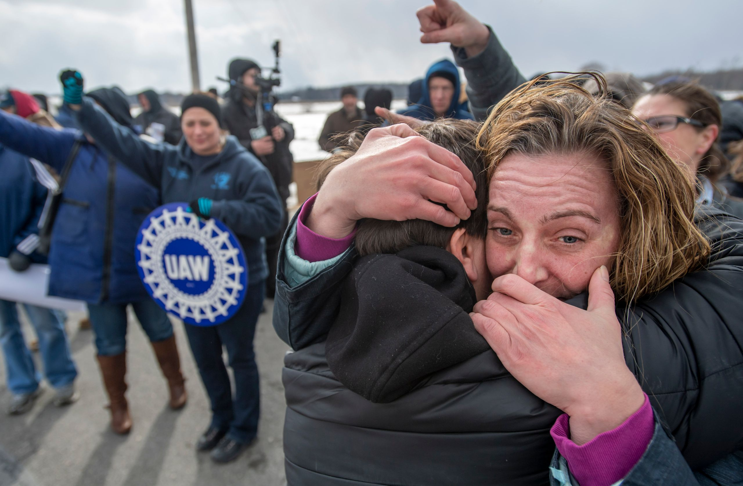 Amy Drennen, right, of Lordstown, Ohio, an employee at General Motors for 12 years, receives a hug from Pam Clark, as people