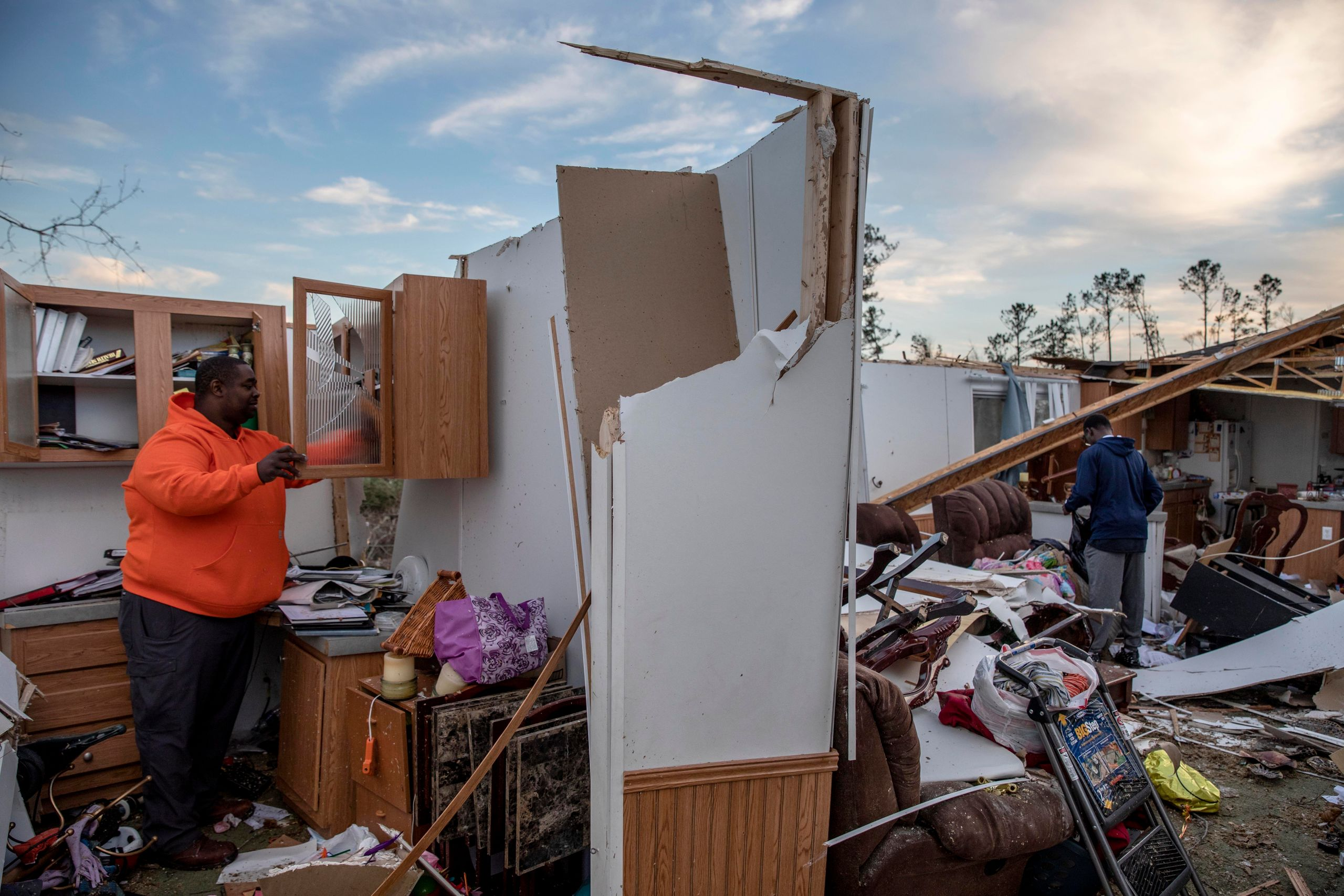 Granadas Baker, left, and son Granadas Jr. 18, right, retrieve personal items from the damaged home where they survived a tor