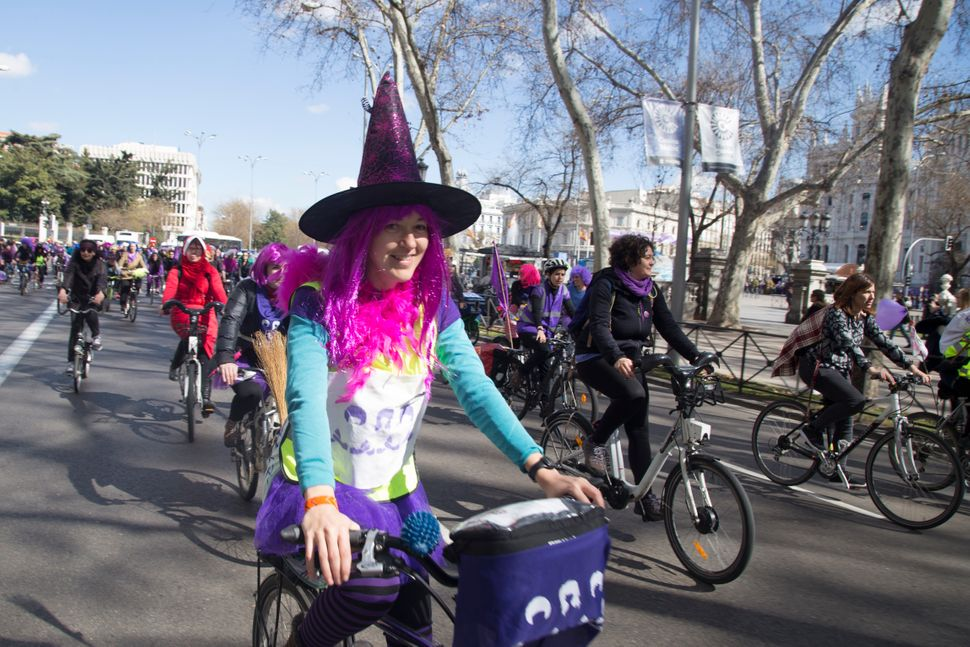 A woman dressed as a witch joins a bicycle demonstration through the streets of Madrid.