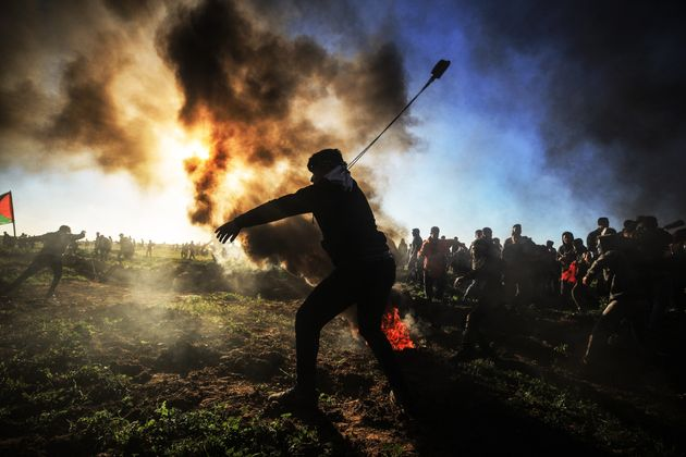 A Palestinian throws a stone with a slingshot toward Israeli security forces during the