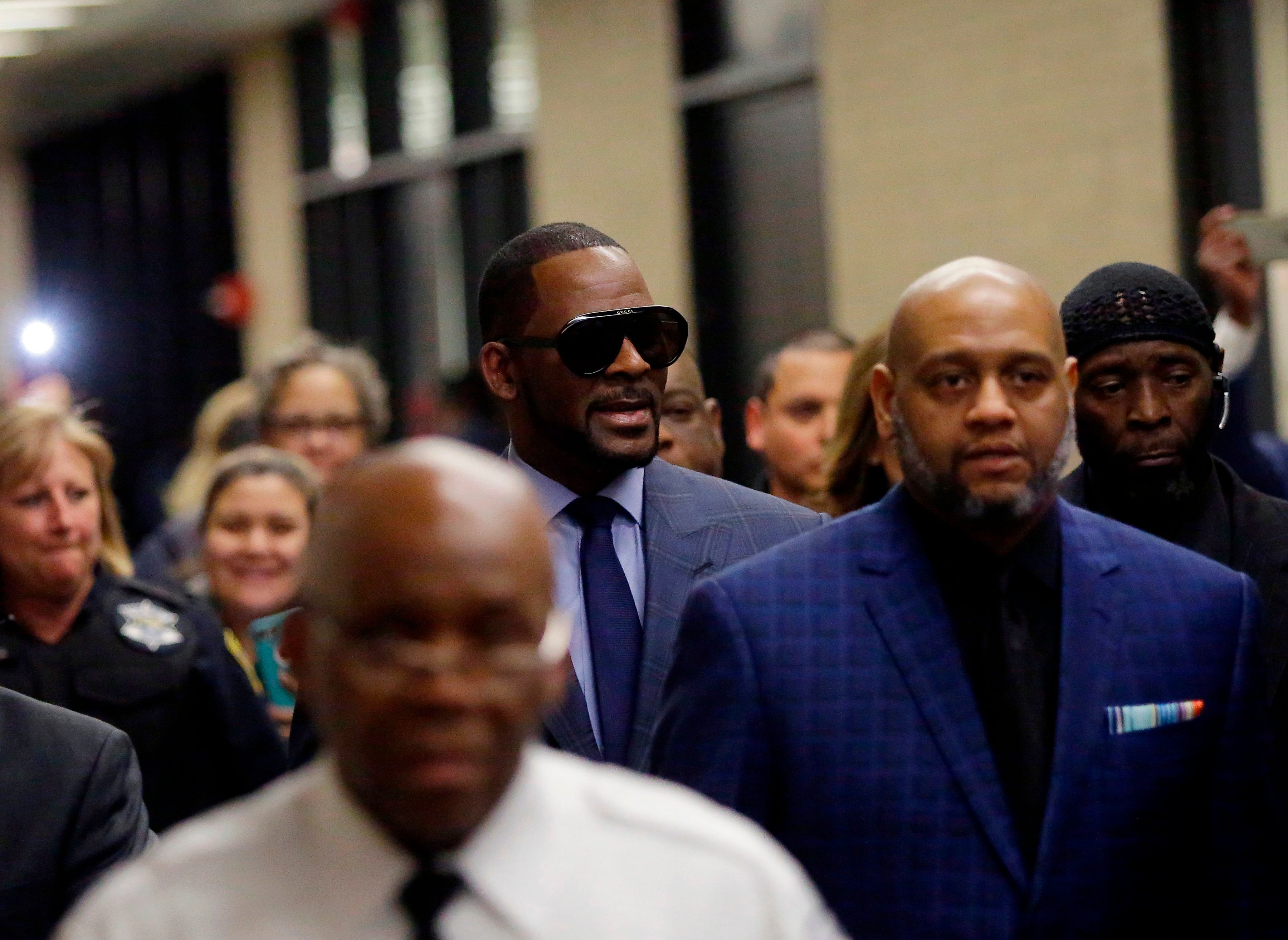 Music artist R. Kelly (C) arrives at the Circuit Court of Cook County, Domestic Relations Division on March 6, 2019 in Chicago, Illinois. - Kelly denied allegations he sexually abused women and girls in his first public comments since being indicted last month. 'I didn't do this stuff. This not me,' Kelly told 'CBS This Morning', saying he was 'fighting' for his life in an interview to air Wednesday. Excerpts were released Tuesday. (Photo by JOSHUA LOTT / AFP)        (Photo credit should read JOSHUA LOTT/AFP/Getty Images)