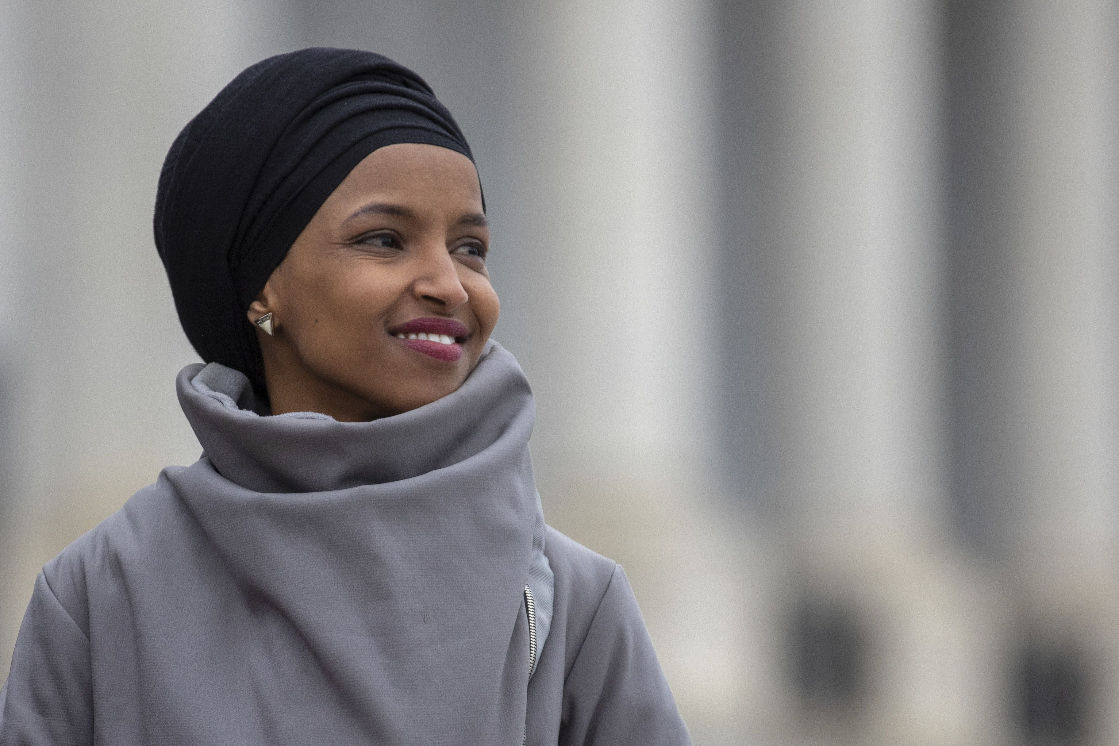 Representative Ilhan Omar, Democrat from Minnesota, smiles during a news conference in Washington, D.C., U.S., on Friday, March 8, 2019. House Democrats are set to approve H.R. 1, a far-reaching elections and ethics bill that would change the way congressional elections are funded, impose new voter-access mandates on states, require groups to publicize donors and force disclosure of presidential candidates' tax returns. Photographer: Alex Edelman/Bloomberg via Getty Images
