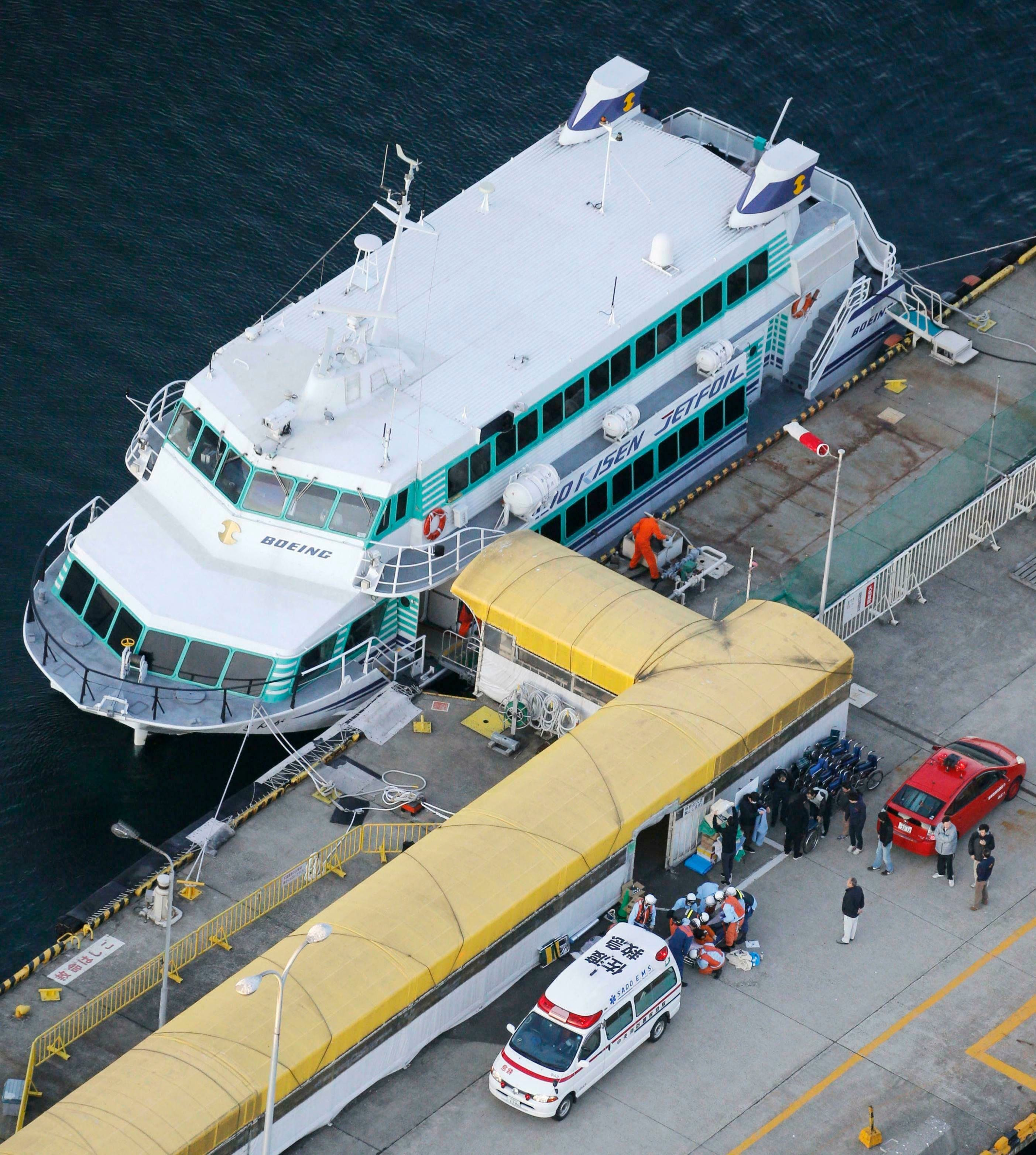 In this Saturday, March 9, 2019, photo, firefighters, bottom, prepare to taken injured passengers to a hospital at a port in Sado city, Niigate prefecture.  A ferry collided with what apparently was a marine animal off a Japanese island on Saturday, injuring more than 80 people, local media reported. The accident happened just after noon off Sado Island, Kyodo News agency reported, citing Japan's coast guard. (Kyodo News via AP)