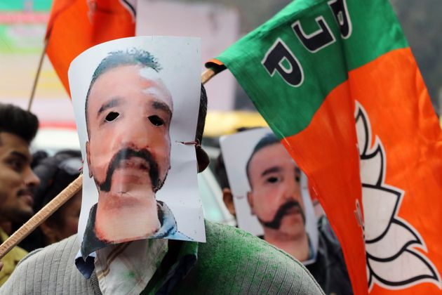 People wear masks in the likeness of Indian Air Force pilot Abhinandan Varthaman and hold Bharatiya Janata...