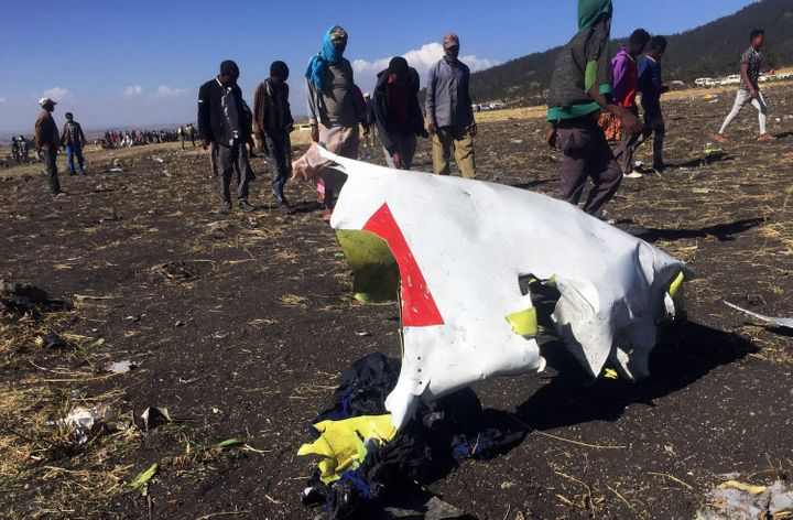 People walk past a part of the wreckage at the scene of the Ethiopian Airlines Flight ET 302 plane crash, near the town of Bi
