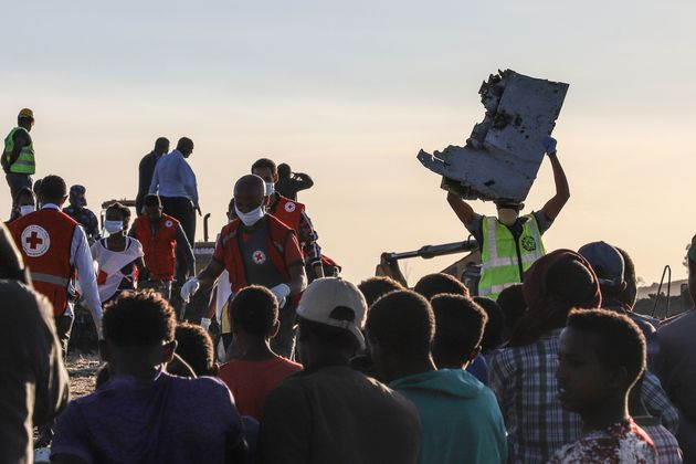 A man carries a piece of debris on his head at the crash site of a Nairobi-bound Ethiopian Airlines flight...