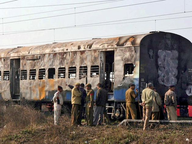 Police officers in front of charred train after explosion on Samjhauta
