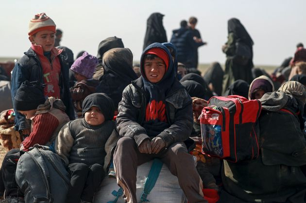 Families fleeing their homes in the village of Baghouz, Syria, for a displaced people's camp nearly...