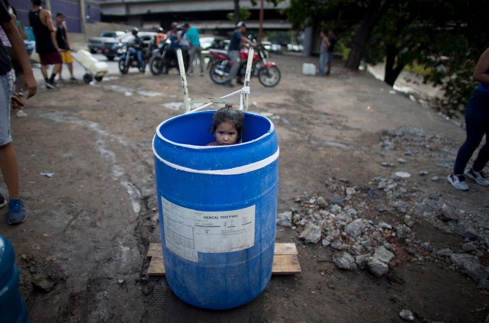 카라카스 구아이레강으로 식수를 구하러 온 한 아이가 플라스틱 통 안에 서서 가족을 기다리고
