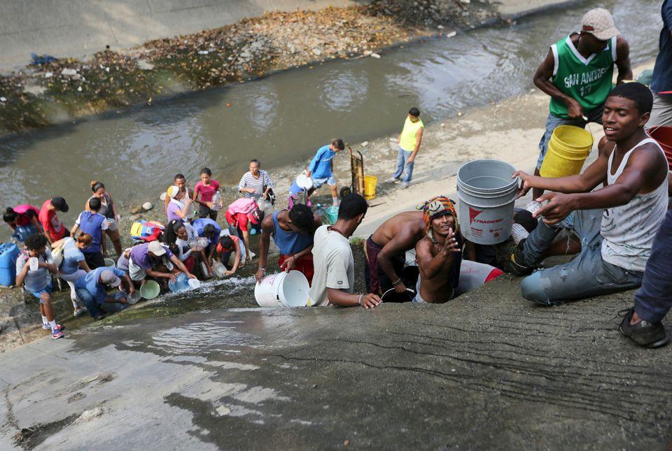 구아이레 강가에서 상수 파이프에서 새는 물을 모으고 있는