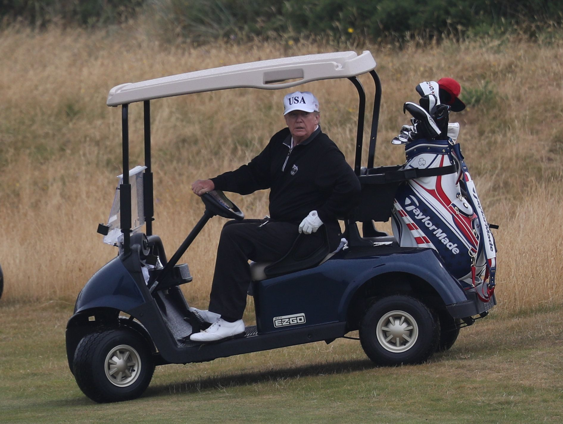US President Donald Trump drives a golf buggy on his golf course at the Trump Turnberry resort in South Ayrshire, where he and his wife Melania, spent the weekend as part of their visit to the UK before leaving for Finland where he will meet Russian leader Vladimir Putin for talks on Monday. (Photo by Andrew Milligan/PA Images via Getty Images)