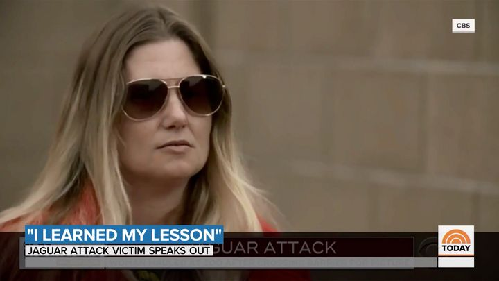 An Arizona woman who was attacked by a zoo's jaguar has apologized, saying she improperly leaned over the safety barrier for