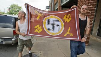 Protestors carry a Nazi flag while marching in Paris, Texas, Tuesday, July 21, 2009.  Protestors and counter protestors marched in this small town over the dismissal of murder charges against two white men in the death of a black man who was run over and dragged. (AP Photo/LM Otero)