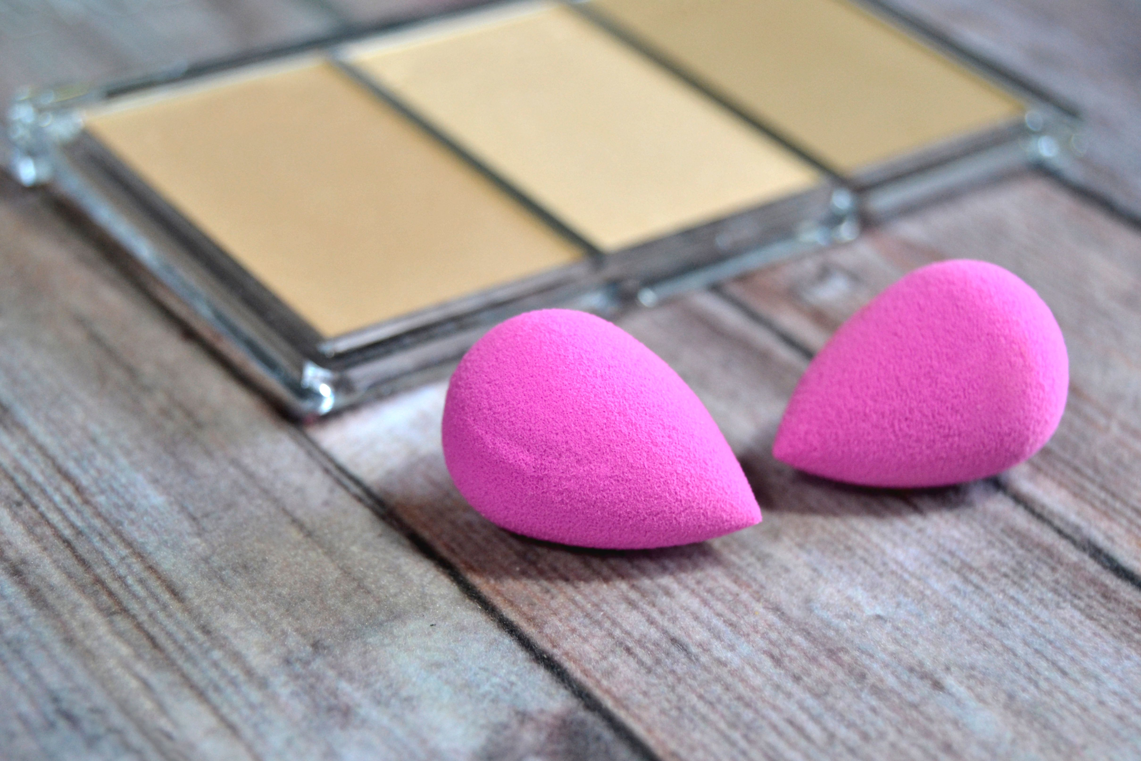 Makeup and makeup sponges on wooden background