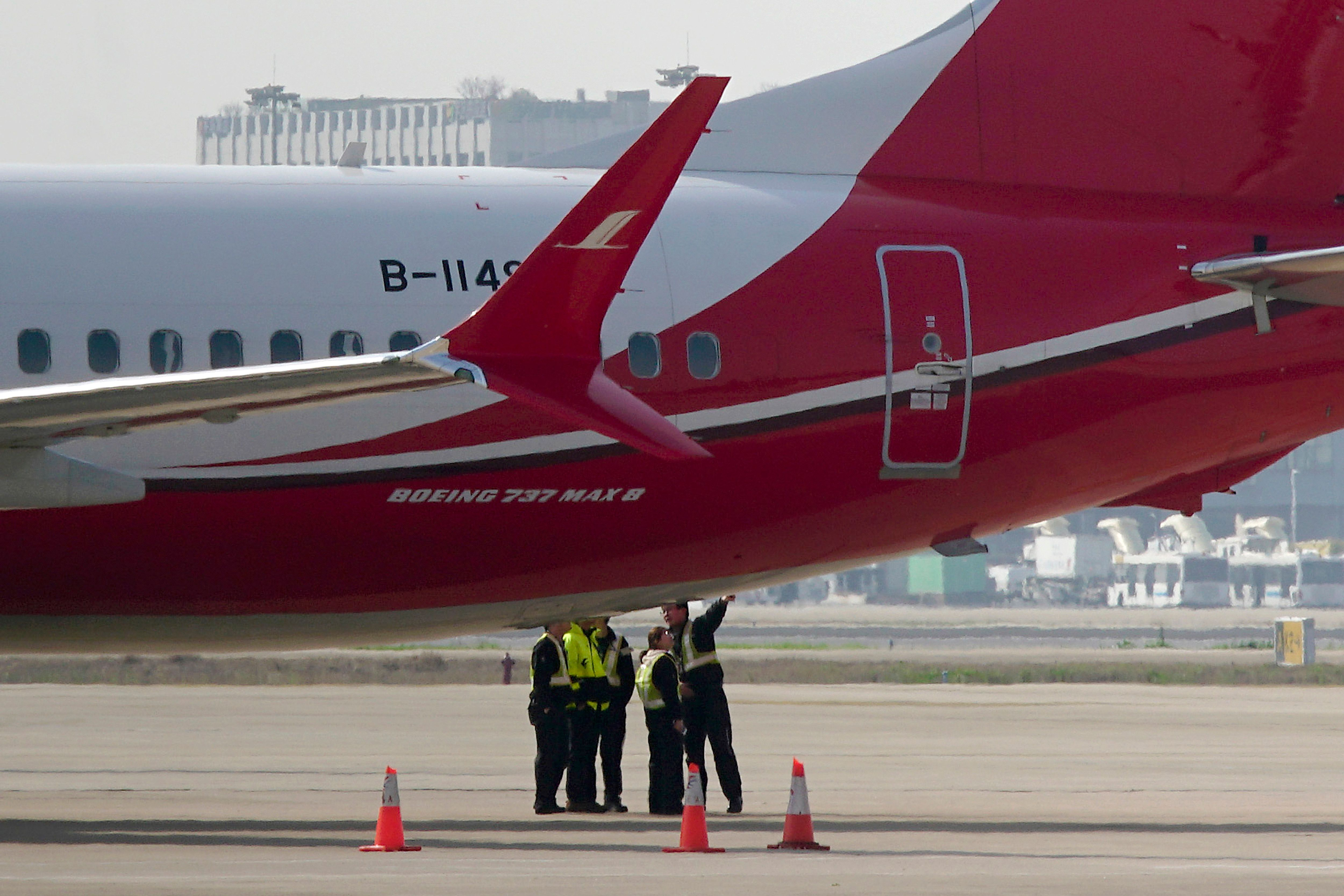 <p> Ground crew chat near a Boeing 737 MAX 8 plane operated by Shanghai Airlines parked on tarmac at Hongqiao airport in Shanghai, China, Tuesday, March 12, 2019. U.S. aviation experts on Tuesday joined the investigation into the crash of an Ethiopian Airlines jetliner that killed 157 people, as a growing number of airlines grounded the new Boeing plane involved in the crash. (AP Photo) </p>