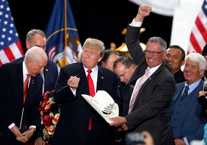 President Donald Trump signs the hat of Bruce Adams, a commissioner of San Juan County, after signing a proclamation to shrin