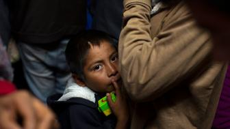 A child looks up while standing next to his relative as they prepare to leave the San Juan Bosco migrant shelter, Sunday, Feb. 24, 2019 in Nogales, Mexico. Most of the people in this shelter were Mexicans from the state of Guerrero who are fleeing gang-related violence in their hometowns and are trying to get asylum in the United States.(AP Photo/Dario Lopez-Mills)