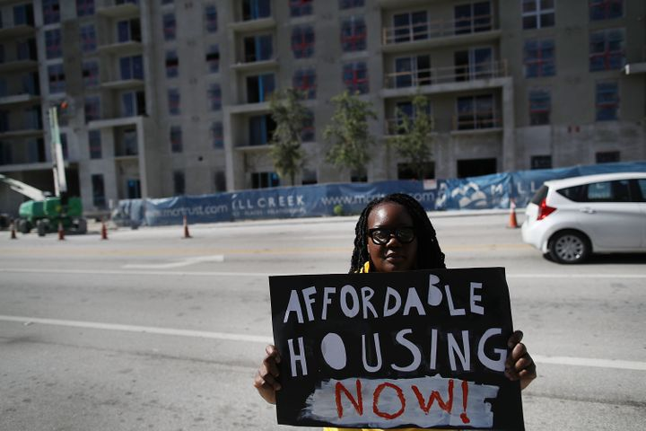 An affordable-housing campaigner outside condos under construction in Miami. The city has one of the nation's largest gaps be