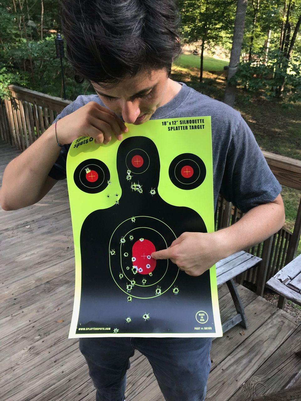 Plaut apontando para o primeiro tiro que deu na vida, direto na mosca com uma arma calibre .22 (razão...