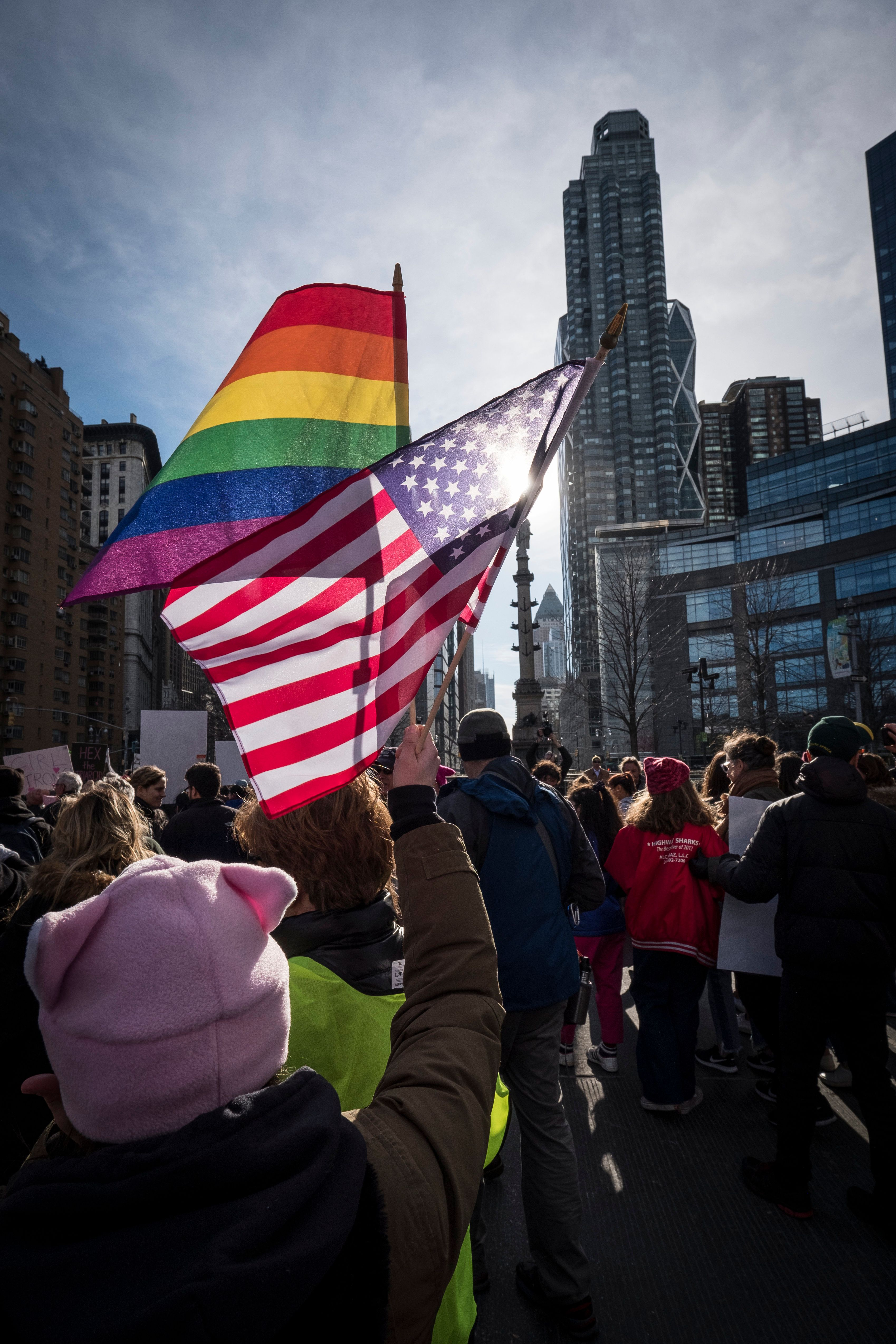NEW YORK, NY - JANUARY 20: A demonstrator holds up a  the American Flag and a Gay Pride Flag in front of Trump International Hotel and Tower during the second annual Women's March in the borough of Manhattan in New York City, U.S. on Saturday, January 20, 2018.  One year after the inauguration of President Donald Trump, thousands of people will again gather to protest for equal rights at the 2018 Women's March.  (Photo by Ira L. Black/Corbis via Getty Images)