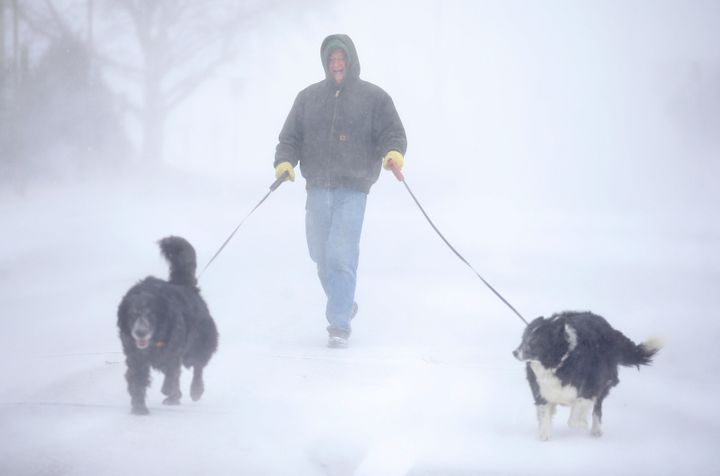 Tom Skaar of Cheyenne laughs while walking his dogs on House Avenue during a blizzard on Wednesday, March 13, 2019, in Cheyen