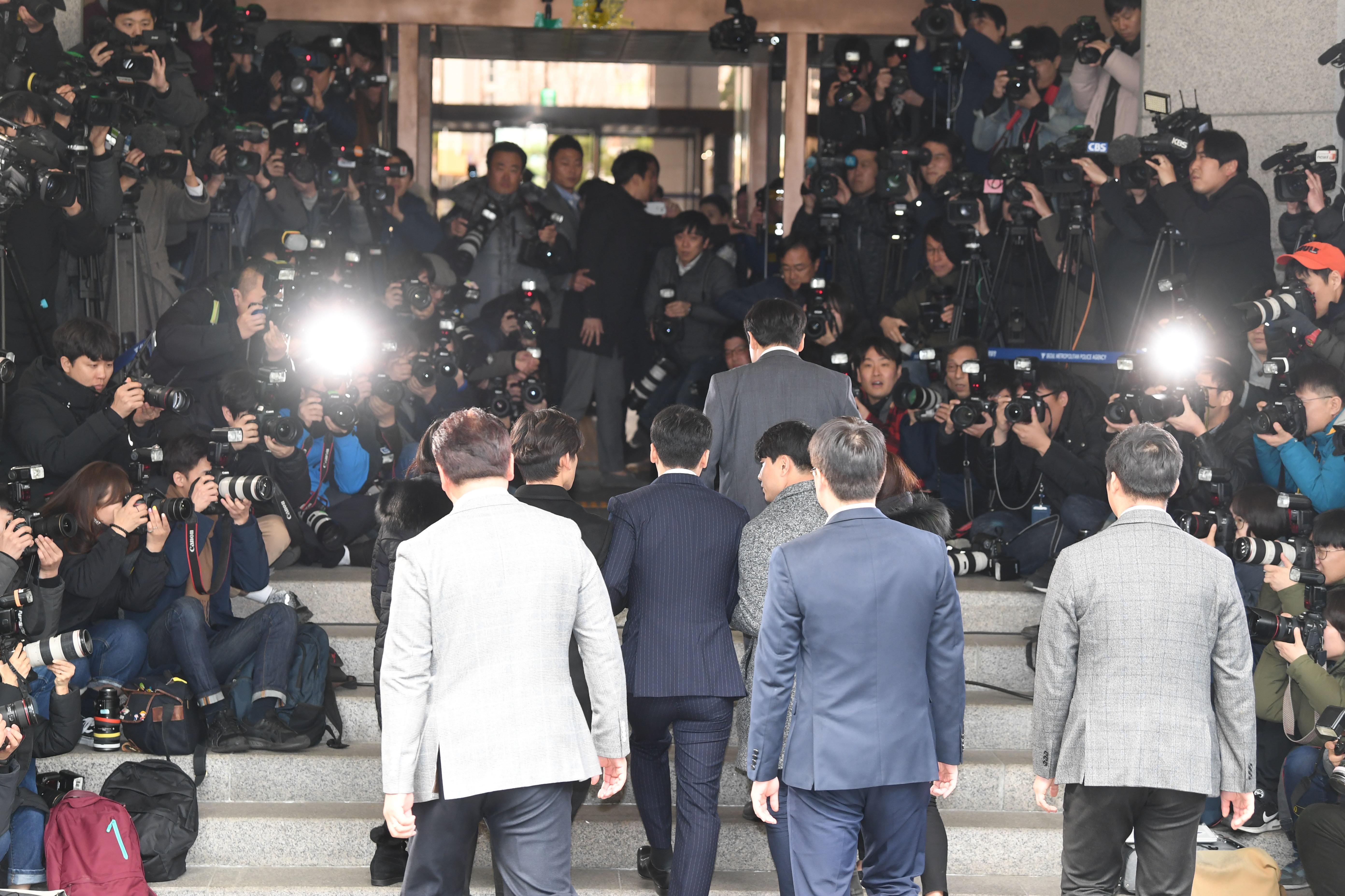 유리홀딩스 대표 유인석씨가 취재진을 피해 경찰에 기습