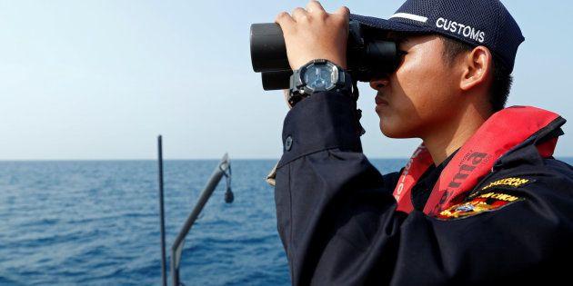 Un agente indonesio, durante la búsqueda del avión de Lion Air en aguas de
