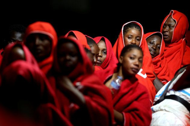 Migrant women, intercepted off the coast in the Mediterranean Sea, wait to disembark the