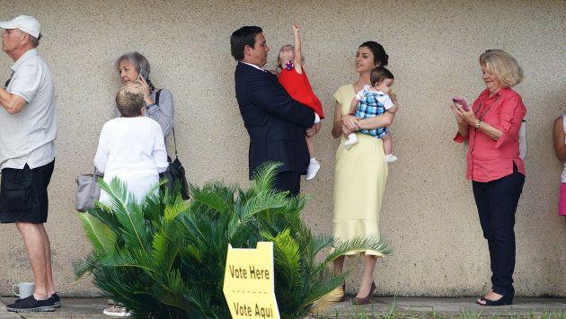 El candidato republicano a gobernador Ron DeSantis (en el centro) espera para votar con su familia en...