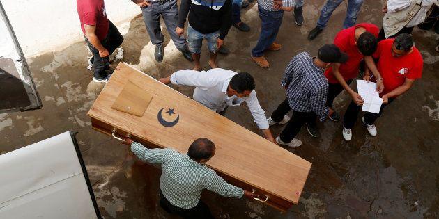 Un grupo de personas traslada el cuerpo de uno de los migrantes ahogados, en la morgue de Sfax,