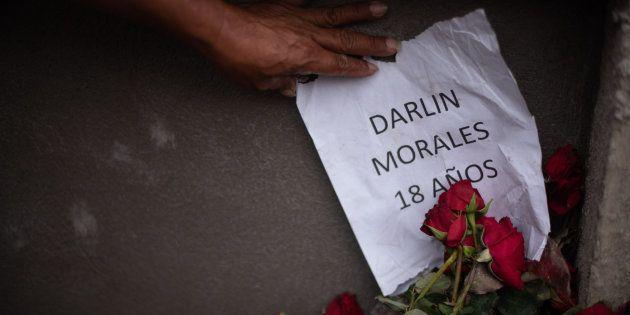 Un encargado de los cortejos fúnebres muestra un papel con el nombre y la edad de una de las