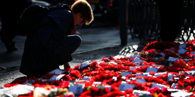 Una mujer deposita flores en una ceremonia para conmemorar el aniversario del fin de la Primera Guerra...