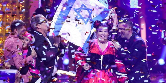 Netta Barzilai, con la bandera israelí de fondo, celebrando su victoria en Eurovisión