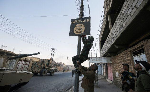 Un miliciano iraquí quita un cartel del Estado Islámico en la población de Tal Afar, al oeste de Mosul,...