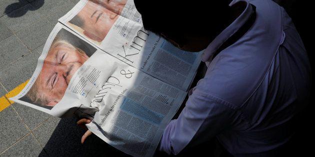 Un hombre lee un periódico con la noticia entre Trump y Kim