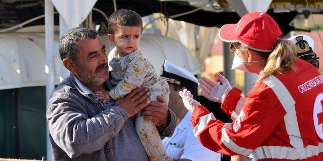 Una miembro de Cruz Roja atiende a un adulto y a un niño a su llegada al puerto de Palermo a bordo del...