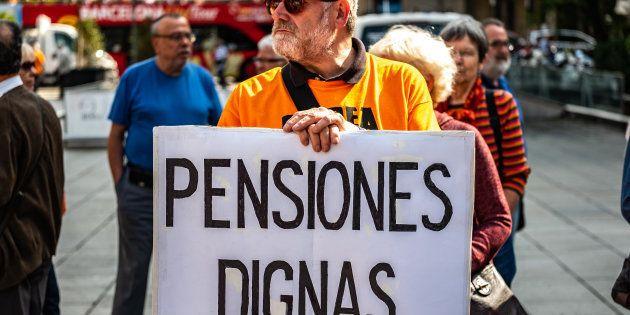 Un manifestante con una pancarta que pide pensiones dignas en una concentración en